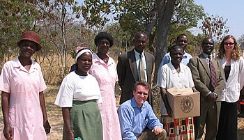 Susanne (far right) and PERSON (kneeling in center) are pictured here delivering books to a Zimbabwean school. The women in pink are the preschool teachers whose training and salaries House Of Stone had funded the three years prior to the visit.